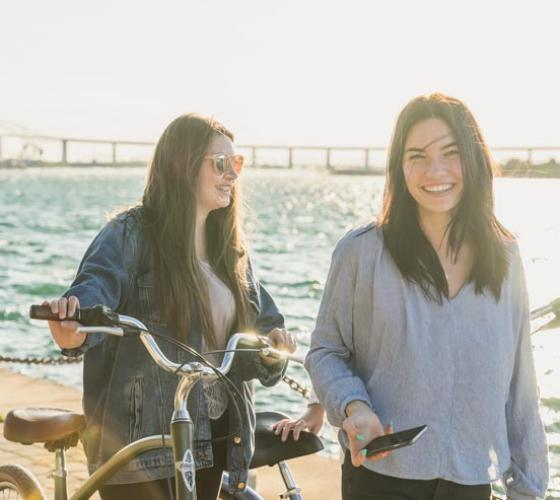 Two young women smiling on the boardwalk.