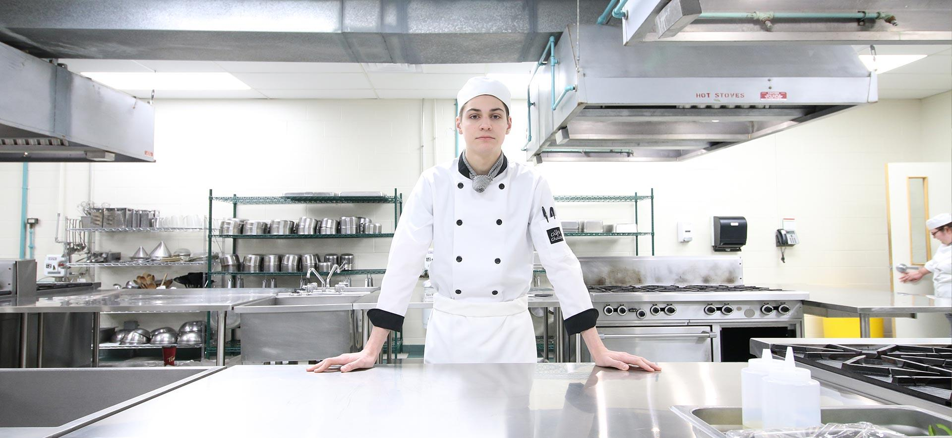 A male Sault College Culinary student poses for a photo in one of the culinary kitchens.