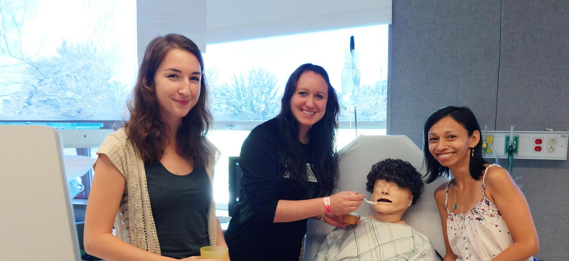 A group of female Personal Support Worker students practice feeding a  healthcare simulation mannequin.