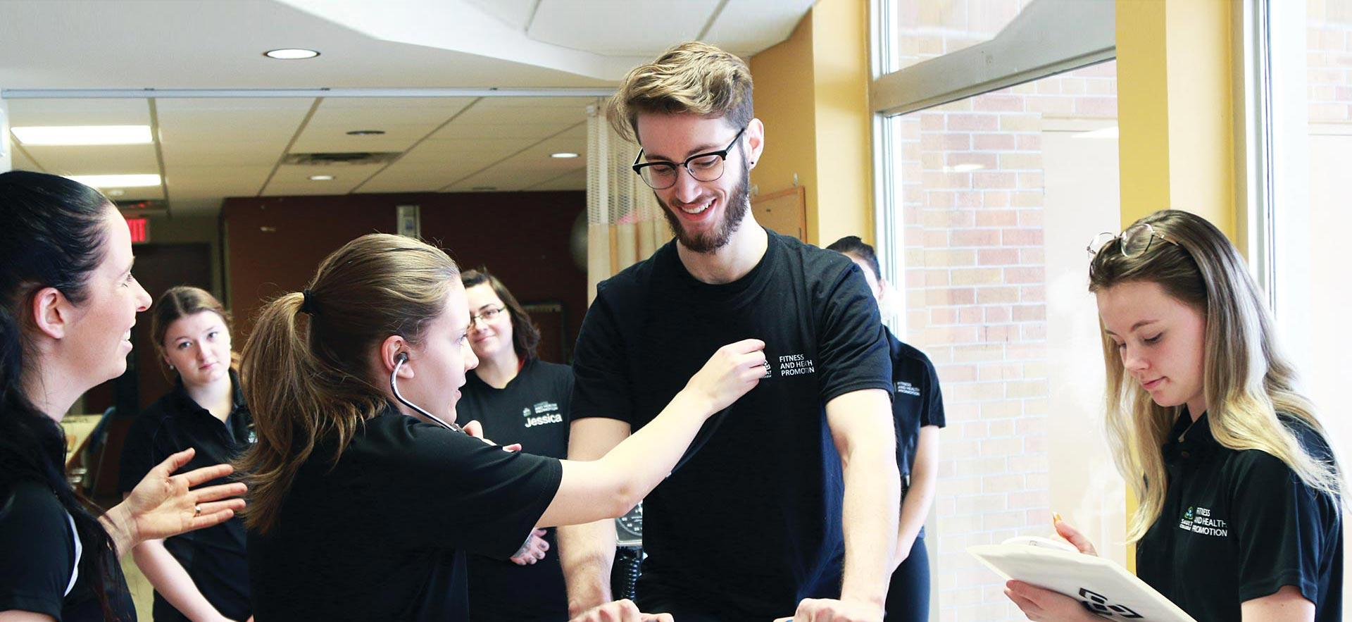 A female Fitness and Health Promotion student checks the  heart-rate of a smiling male student.