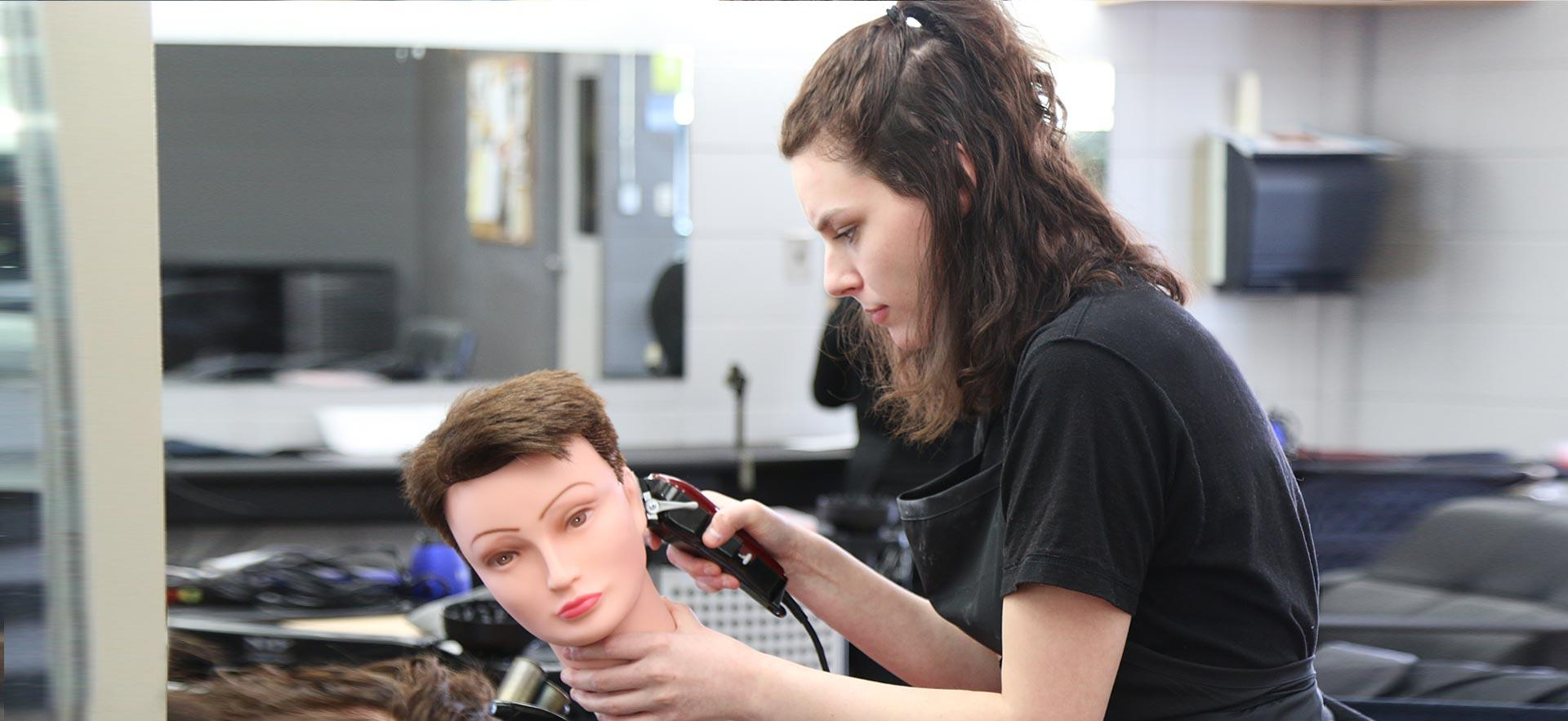 One female hairstylist student cuts the hair of a mannequin in class.