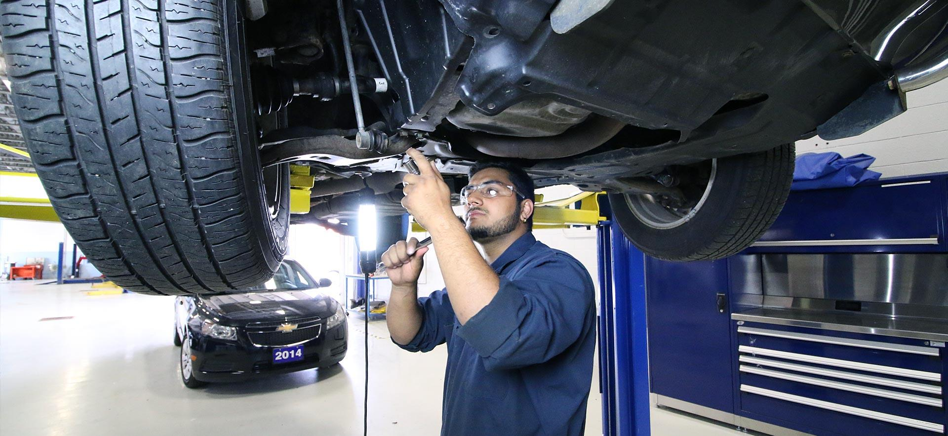 One male Motive Power Fundamentals - Automotive Repair student works a car thats on a lift.