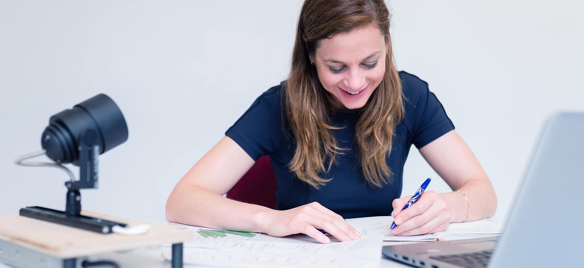 A female business writer smiles as she works on a project.