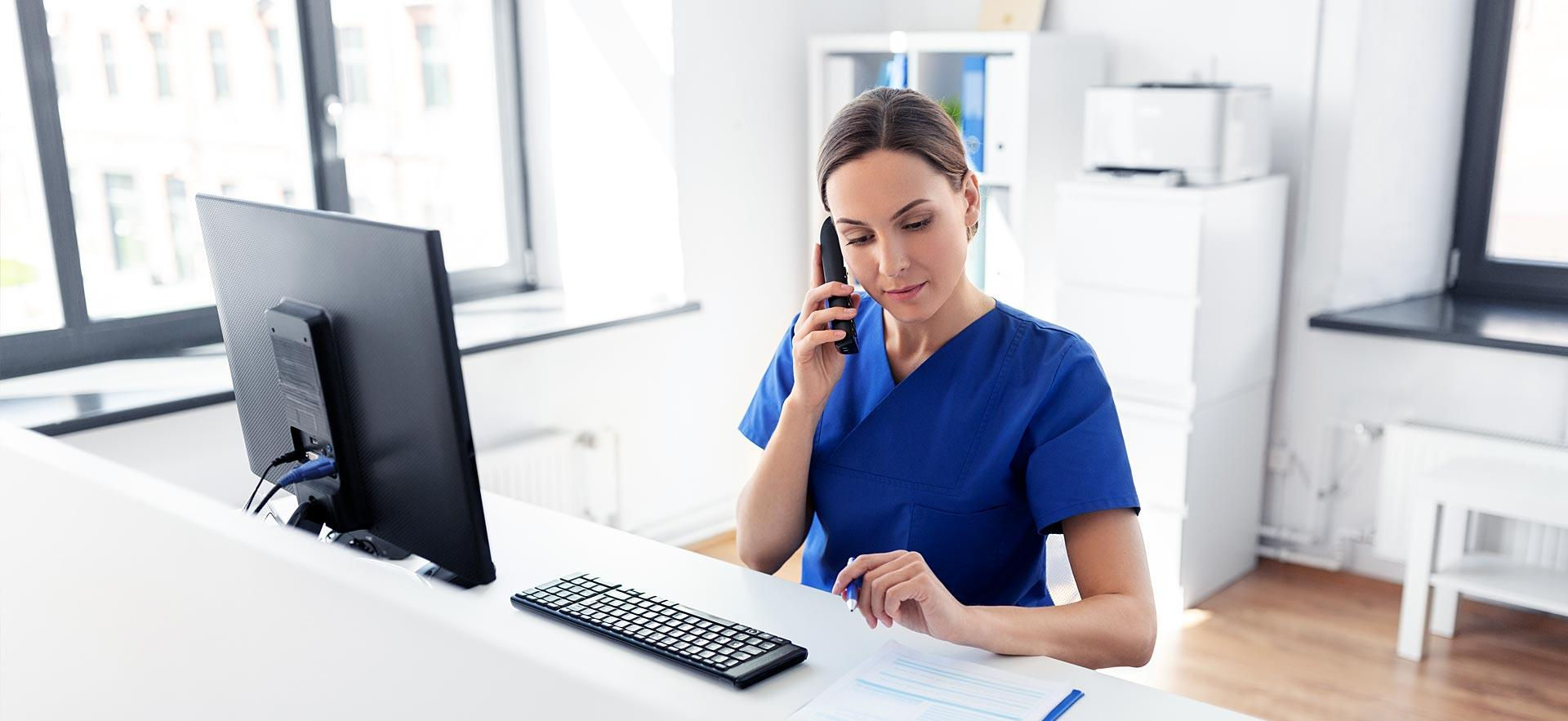 Female health office worker answers phone at her desk.