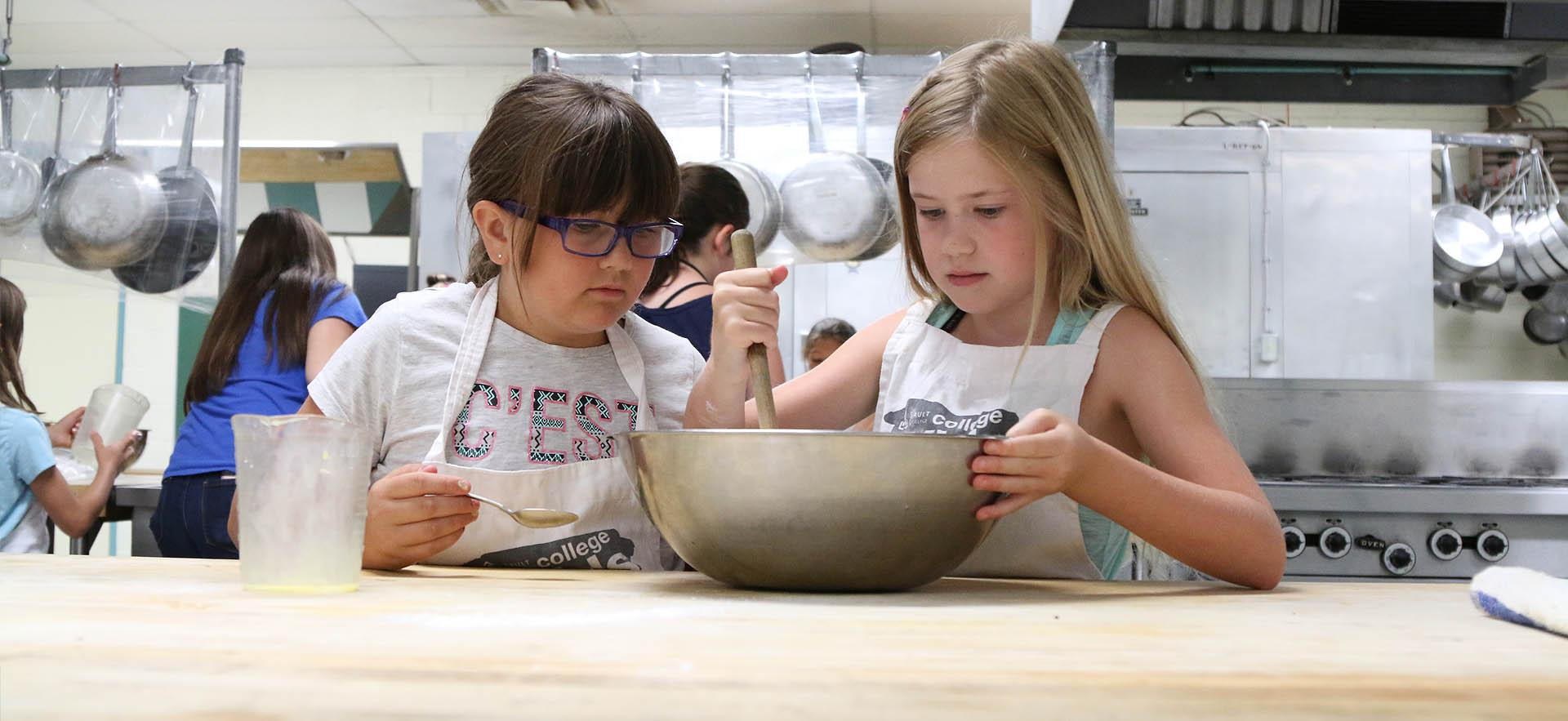 Kids camp students looking at bowl in culinary class