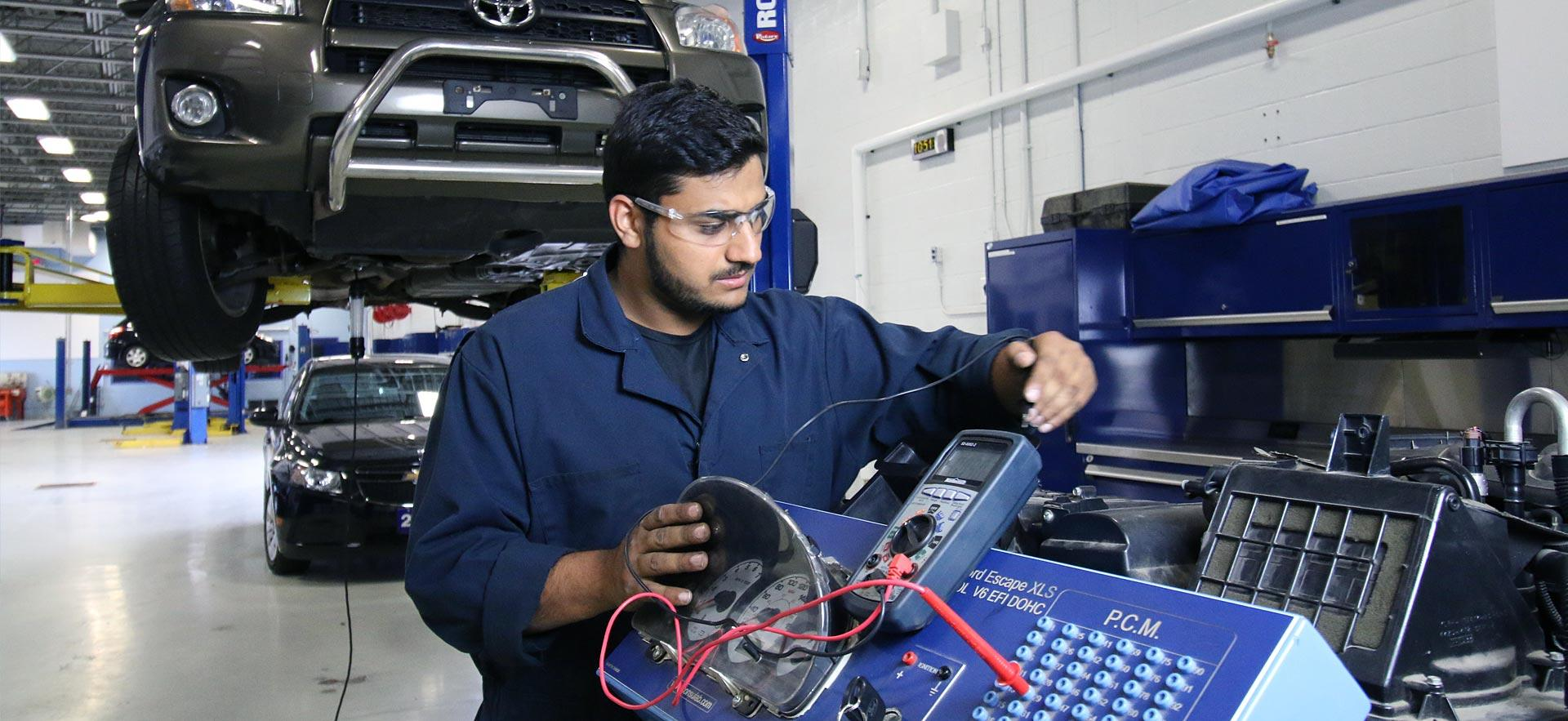 A male Motive Power Fundamentals - Automotive Repair student works on an engine.