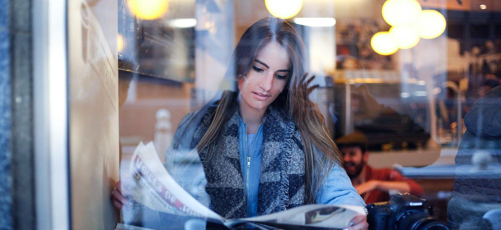 Young woman reding a newspaper in a cafe.