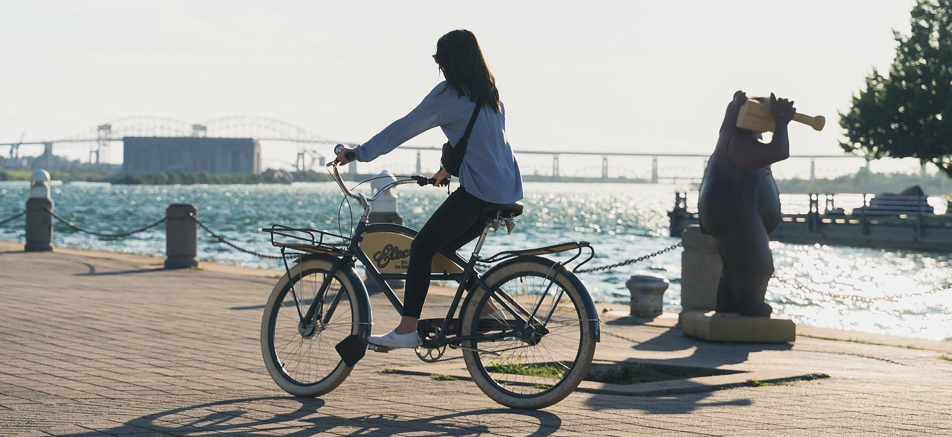 Young woman riding her bike on the boardwalk.