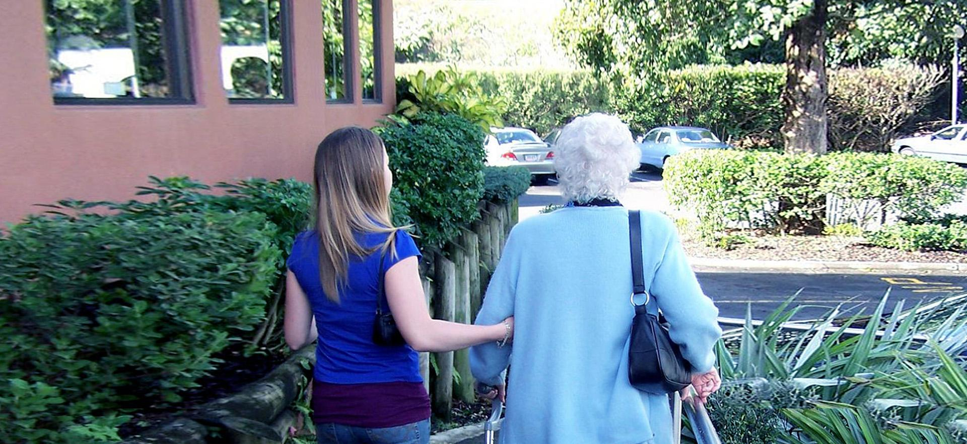 A young female helps an elderly woman walk down a sidewalk.