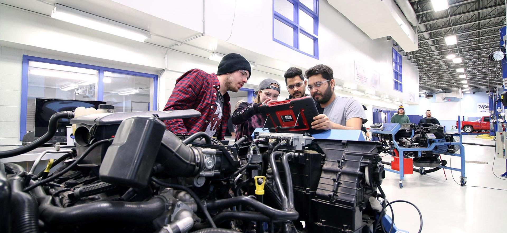 A group of male Motive Power Technician - Advanced Repair students run diagnostics on a car engine.